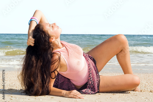 The young woman lies on sand at sea coast