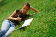 Beautiful young woman in green field with notebook.