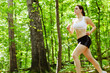 Beautiful young woman runner in a green forest.