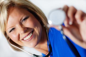 Mature nurse in scrubs holding up stethoscope.