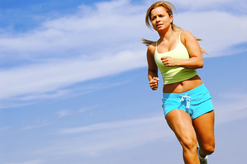 Beautiful young woman running against blue sky.