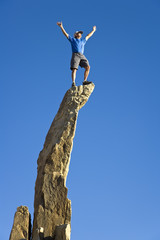 Man on the summit of a rock spire.