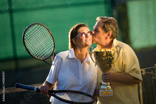 Active senior couple is posing on the tennis court