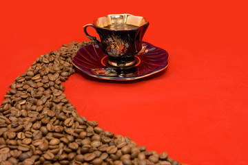 Coffee beans and a cup of coffee lying on the red background