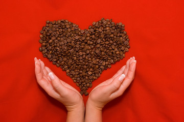 Heart made of coffee beans lying on the red background