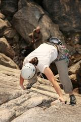 A female climber leads a challenging rockclimb.
