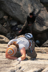 A female climber reaches for a higher hold.