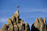 Climber on the summit of a rock spire. poster