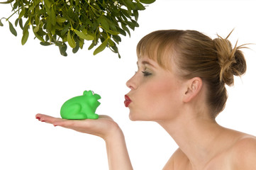 Naked model kissing a frog under mistletoe isolated on white