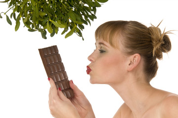 Naked model kissing chocolate under mistletoe