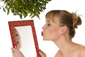 Naked model kissing herself in a mirror under mistletoe