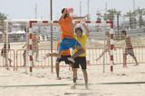 Fototapety Handball player jumping with the ball on a handball beach matc