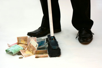 a man in business suit sweeps money with mop