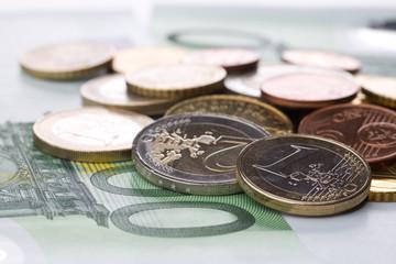 Verschiedene Euromünzen liegen auf 100 Euro Geldschein