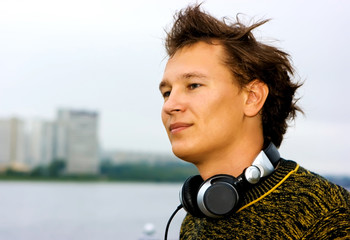 DJ Roman Kravtsov touching his headphones and standing