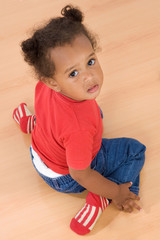 Adorable african baby sit over wooden floor