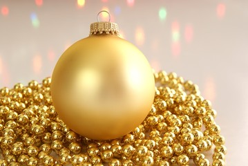 Gold Christmas ornament surrounded by gold beads