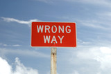 Wrong Way sign against blue sky poster