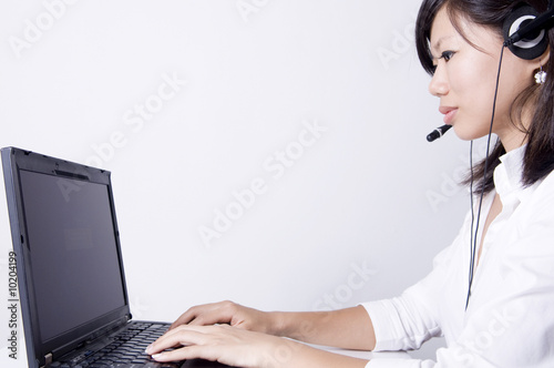 Asian consultants with headsets working on laptop computer .