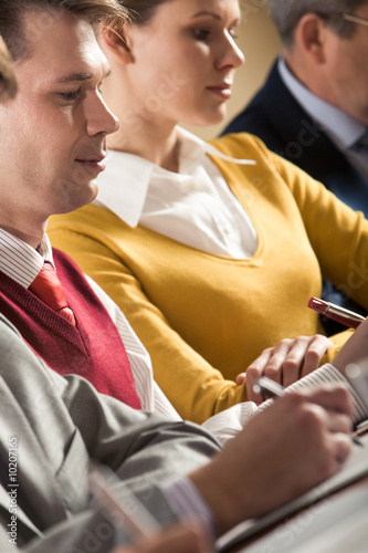 Confident businessman writing summary of his work