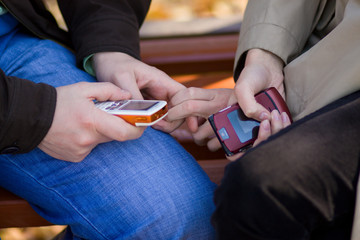 Youngs man and woman hands hold mobile phones