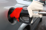 Bright red gas pump inserted into an automobile gasoline tank poster
