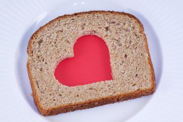 Red heart pattern cut in a slice of  bread