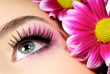 Close-up of woman green eye. Pink flower on background.