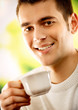 Portrait of young man with cup of tea or coffee