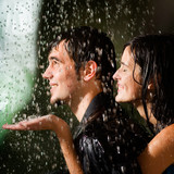 Young happy amorous couple hugging under a rain