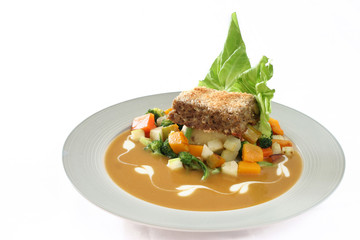 Gourmet meatloaf on a bed of vegetables