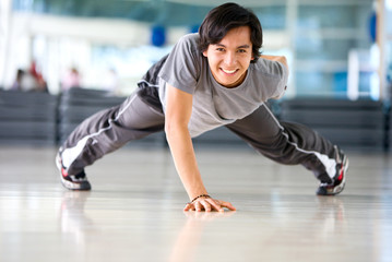 man at the gym doing stretching exercise
