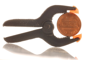 penny squeezed in a clamp - penny pinching