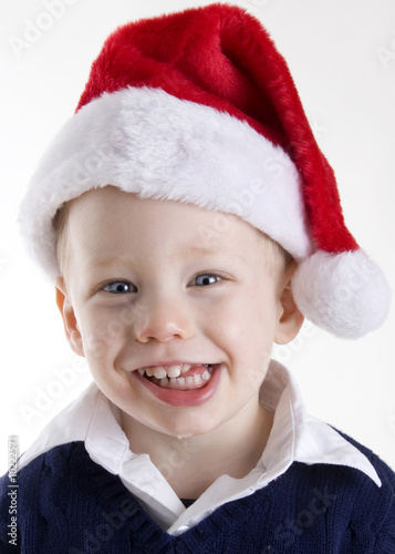 Handsome young child wearing a red santa claus hat