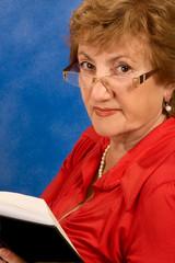 Mature attractive woman in glasses reading book