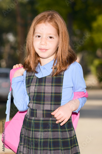 Elementary age schoolgirl in uniform with backpack