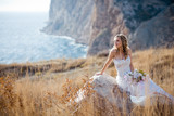 Fototapety Beautiful bride sitting on stone at field over mountains and sea