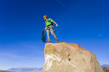 Climber on the summit of a rock spire.