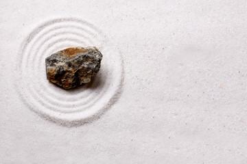 A simple zen rock garden design with a rough stone
