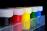 Tubes of colorful acrylic paint isolated on black background poster