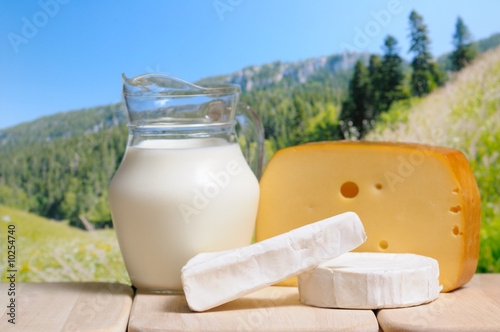 Milk jug and cheese against a mountains in background