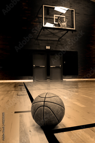 Basketball on court with hoop in the background