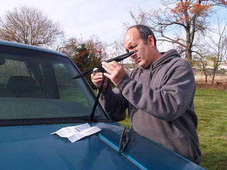 man installing new windshield wipers on a car
