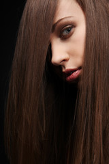 Beautiful young woman with long healthy dark hair .