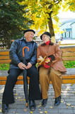 happy grandparent on bench in park poster