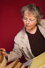 Mature woman with heaps of books and note pad