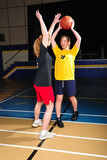 Two women playing basketball in gymnasium poster
