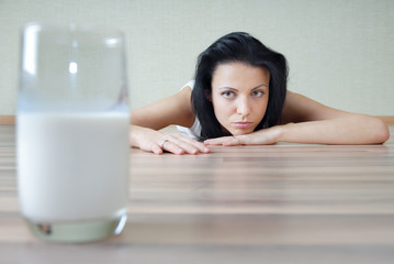 Photo of the glass with milk and woman laying on a parquet floor