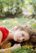 beautiful young woman lying on the grass with yellow leaves