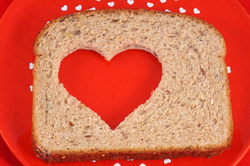 Slice of whole wheat bread with heart shape cut out of center.